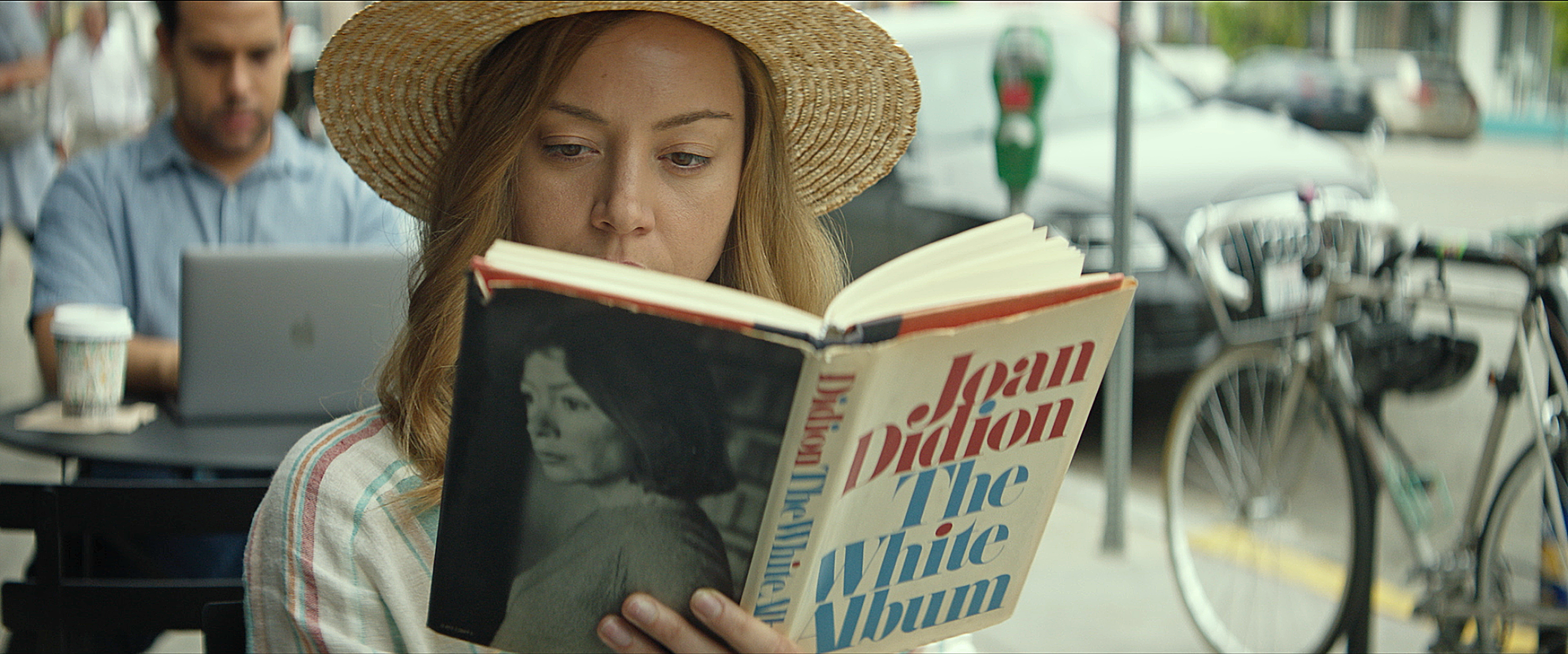 Ingrid (Aubrey Plaza) reads in a public place in INGRID GOES WEST, courtesy of NEON